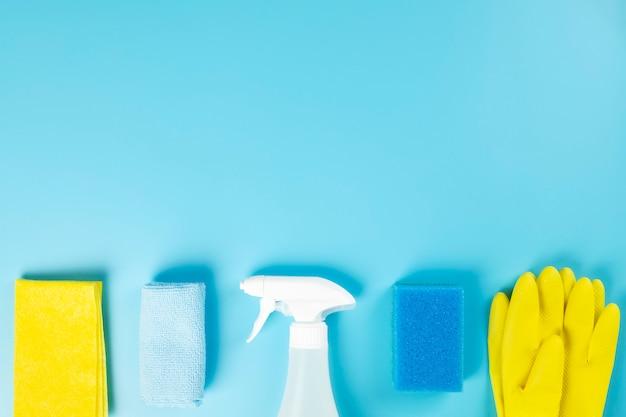 洗剤、洗浄剤、スポンジ、ナプキン、ゴム手袋、青色の背景色。上面図。コピースペース