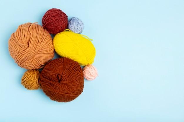 編み物、編み針、かぎ針編みのフック、青色の背景色の糸。上面図。コピースペース