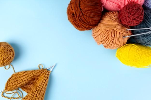 編み物、青色の背景色の糸。編み物プロジェクトが進行中です。上面図。コピースペース