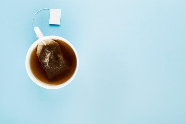 一杯の紅茶と青色の背景にティーバッグ。上面図、コピースペース