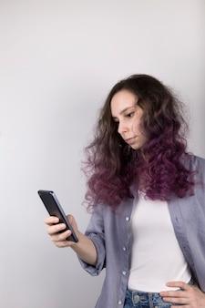 Молодая девушка задумчиво смотрит в телефон. кудрявая окраска фиолетовых волос. серый
