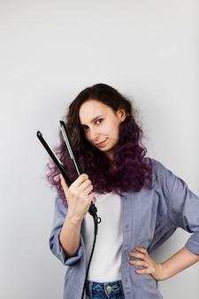 若い女の子はフラットアイアンの巻き毛を整えます。紫色の髪を着色します。グレー