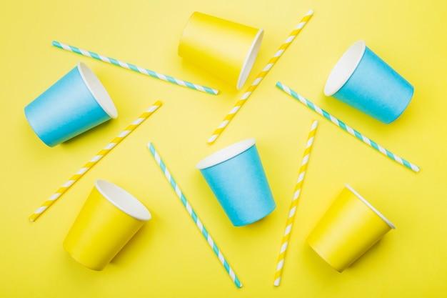 Синие и желтые бумажные стаканчики и соломы на синем. вид сверху