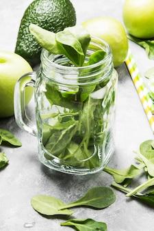 緑のスムージー - リンゴ、ほうれん草、セロリ、明るい背景にアボカドのための原料