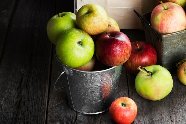 金属製のバケツに様々な熟したリンゴ