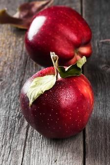 暗い木製の表面に赤いリンゴ