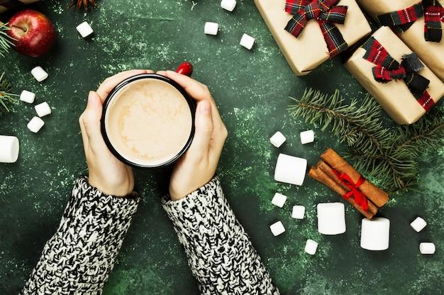 ホットチョコレートと緑の表面に休日のさまざまな属性を持つカップを保持している女性の手