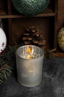 Горящая свеча в подсвечниках и рождественские атрибуты на темной поверхности