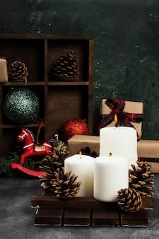 Горящие свечи и рождественские атрибуты на темной поверхности