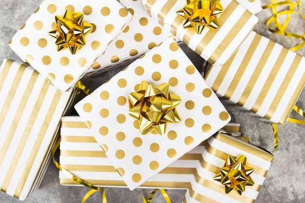 Группа подарков из белой и золотой бумаги на сером, вид сверху