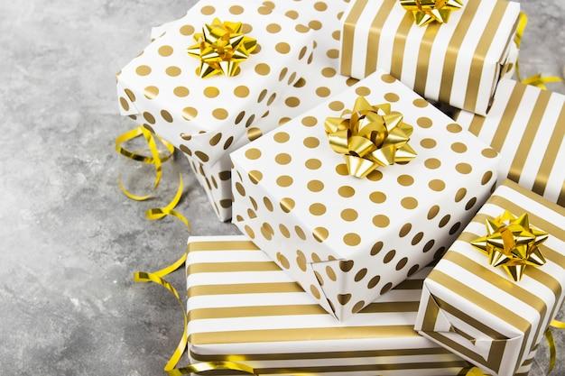 Группа подарков в белой и золотой бумаге на сером, копией пространства