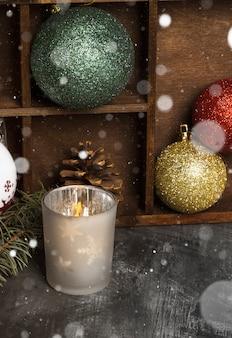 Горящая свеча в подсвечниках и новогодняя атрибутика на темном снегу