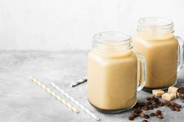 灰色の背景に背の高いグラスにミルクとアイスコーヒー。スペースをコピーします。食品の背景