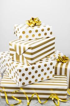 Группа подарков в белой и золотой бумаге на сером