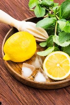 レモン、ミント、木製の背景に木製のトレイに氷