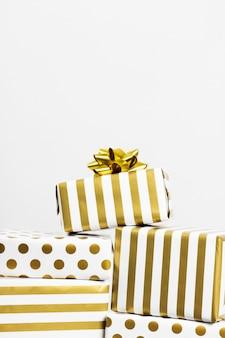 Группа подарков в белой и золотой бумаге на серой поверхности