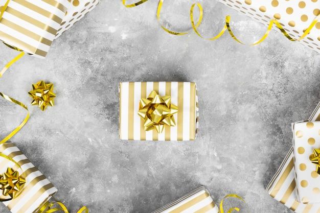 Группа подарков в белый и золотой бумаги на серой поверхности. вид сверху
