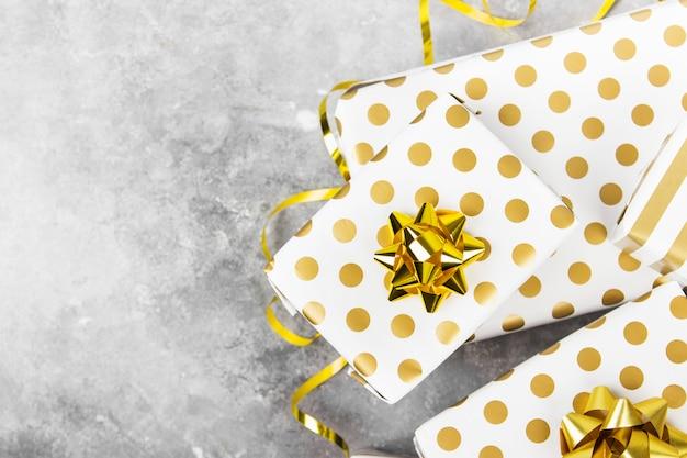 Группа подарков в белый и золотой бумаги на серой поверхности. вид сверху, копия пространства