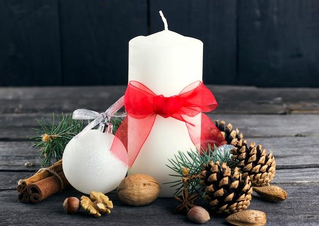 Праздничные свечи, еловое дерево, сосновые шишки, орехи на деревянной поверхности