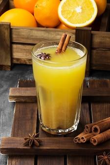 Зимой горячий напиток из апельсинов и специй на черной поверхности.