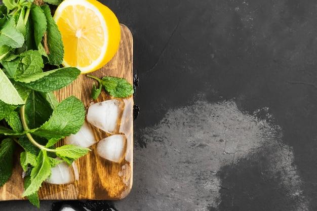 レモン、ミント、暗い背景に木製のまな板の上の氷