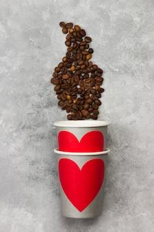 コーヒーのコンセプトが大好きです。赤いハート、明るい背景にコーヒー豆と飲み物の灰色の紙コップ。上面図。食品の背景