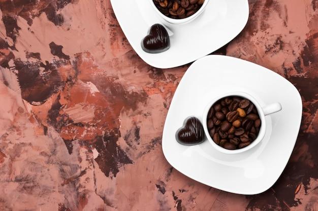 ハートの形のコーヒー豆とチョコレートで満たされたエスプレッソの白いカップ。トップビュー、コピースペース
