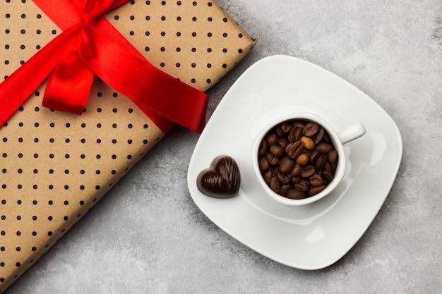 白いカップのコーヒー、赤いテープとチョコレートのギフト。上面図。食品の背景