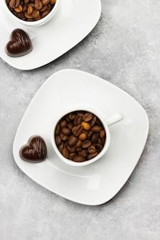 明るい背景にハートの形のコーヒー豆とチョコレートで満たされたエスプレッソの白いカップ。上面図。