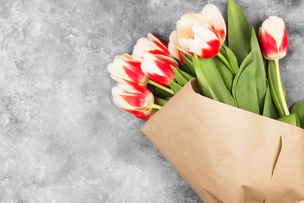 明るい背景にクラフト紙で赤白チューリップの花束。トップビュー、コピースペース
