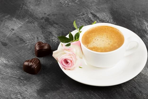 白いカップにエスプレッソコーヒー、暗い背景にピンクのバラとチョコレート。コピースペース