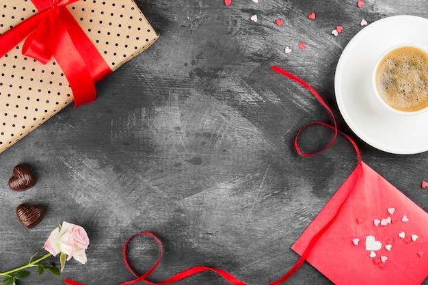白いカップ、ピンクのバラ、赤いテープと暗い背景にチョコレートの贈り物にエスプレッソコーヒー。トップビュー、コピースペース。食品の背景。