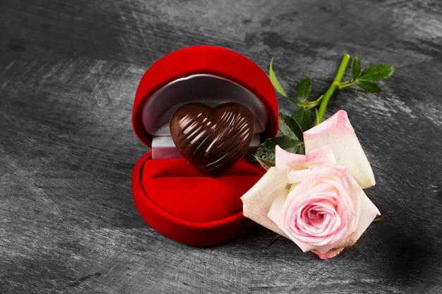 リングの赤いケースにハートの形のチョコレート、暗い背景にピンクのバラ。チョコレートのコンセプト愛
