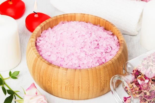 木製ボウル、花びら、新鮮なピンクのバラ、タオル、白い背景の上のキャンドルの香りの入浴剤