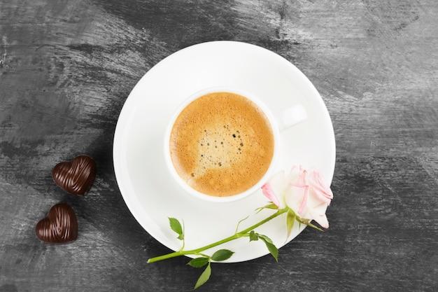 暗い背景に白いカップ、ピンクのバラ、チョコレートのエスプレッソコーヒー。上面図。食品の背景。