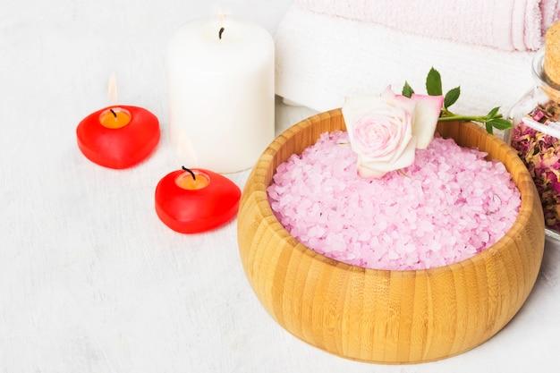 Соль для ванн с ароматом розы в деревянной миске, лепестки и свежая розовая роза, полотенца и свечи на белом фоне