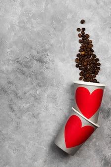 コーヒーのコンセプトが大好きです。赤いハート、明るい背景にコーヒー豆と飲み物の灰色の紙コップ。トップビュー、コピースペース。食品の背景