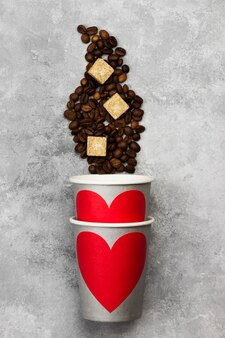 コーヒーのコンセプトが大好きです。赤いハート、明るい背景にコーヒー豆と飲み物の灰色の紙コップ。上面図。食品の背景。
