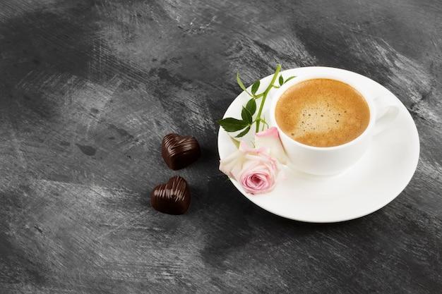 暗い背景に白いカップ、ピンクのバラ、チョコレートのエスプレッソコーヒー。コピースペース