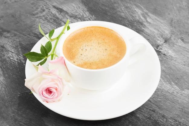 白いカップと暗い背景にピンクのバラのエスプレッソコーヒー。