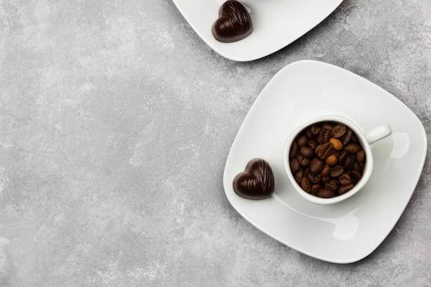 ハートの形のコーヒー豆とチョコレートで満たされたエスプレッソの白いカップ。トップビュー、コピースペース。食品の背景