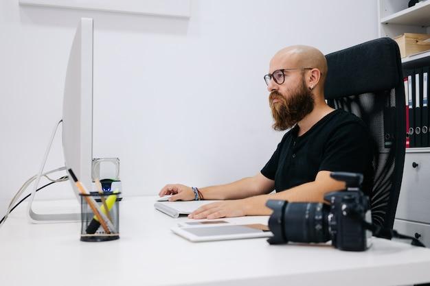男の写真家の仕事でコンピューターを使用します。