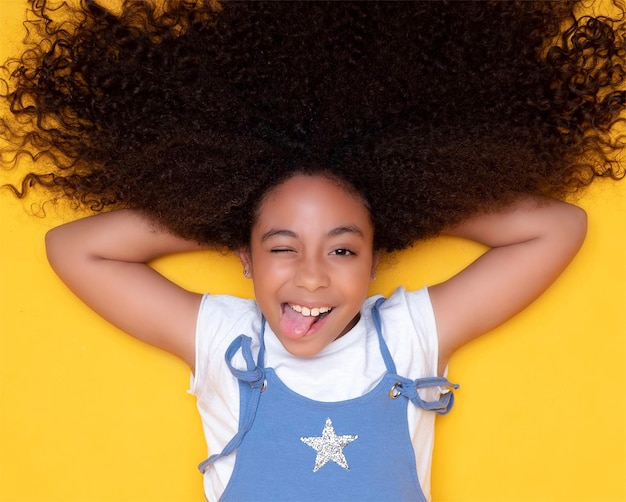 巻き毛のかわいいアフリカ系アメリカ人の女の子は笑顔し、彼女の舌を突き出します