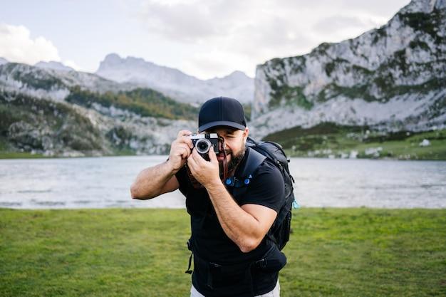 Мужчина фотографирует в горном пейзаже