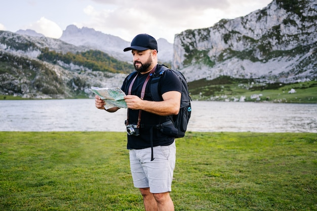 Мужчина смотрит на карту в горном пейзаже