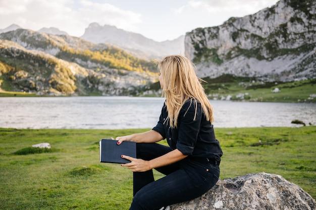 Красивая кавказская белокурая женщина читает книгу в гористом ландшафте с озером