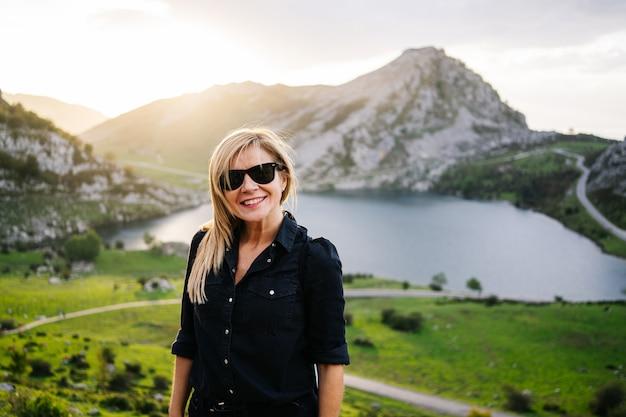Красивая кавказская белокурая женщина нося вскользь одежды в гористом ландшафте с озером