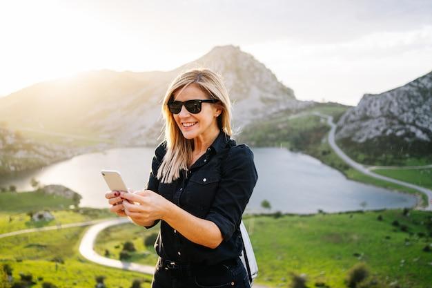 Красивая кавказская белокурая женщина использует телефон в гористом ландшафте с озером