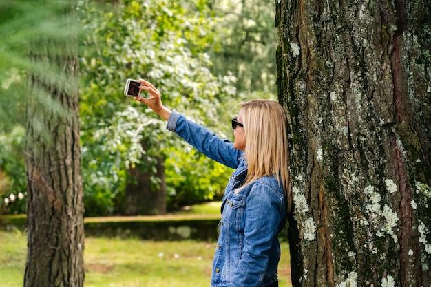 Женщина использует телефон, чтобы сделать селфи в парке