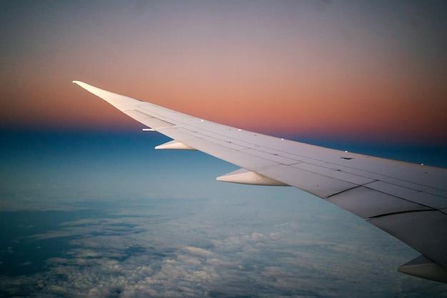 Крыло самолета видно из окна во время полета на рассвете